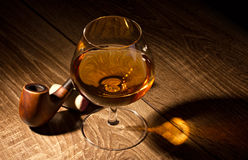 Glass with brandy and tobacco pipe Stock Photo