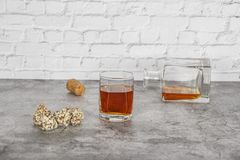 A glass of brandy or whiskey on a background of gray stone with truffles. Place for text.  royalty free stock images