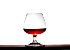 Glass with brandy on a white background. Glass with brandy on a white bright background Royalty Free Stock Photography