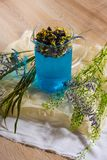 A glass brewer full of blue butterfly pea tea, with purple flowers and green branches next to it, on crumpled wrapping paper on royalty free stock images