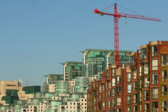 Glass and brick buildings with red crane Stock Photo