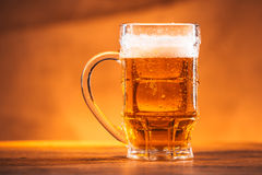 Glass bright beer mug on a blurred background Stock Photography