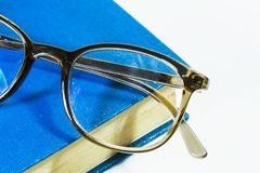 Glass. Brown glasses on a blue book good for  editing Stock Photos