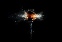 Glass with brown liquid exploded. By bullet with many splashes around at the black background Stock Image