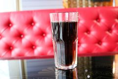 Glass with a brown, sweet, cold, carbonated drink on a table in a cafe in the evening on the background of a red sofa. A glass glass with a brown, sweet, cold Stock Photography