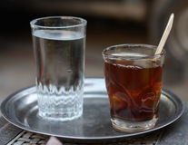 Glass of tea and water. Side view of glass of tea and water on silver plate Royalty Free Stock Photo