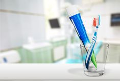 Toothbrush and toothpaste in glass on blurred Royalty Free Stock Images