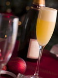 Glass of Bucks Fizz. With bottle in the background royalty free stock photos
