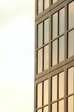 Glass window building. Close-up of a glass window building side. The windows are reflecting a clear background Stock Photography