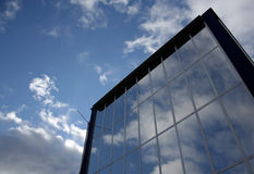 Glass building. Modern glass office building on cloudy sky Stock Photo