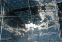 Glass Building. Building facade with glass windows against clouds and sun Stock Images