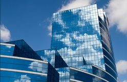 Glass Building in Blue. Clouds and blue sky reflect in the windows of a contemporary office building Royalty Free Stock Photography