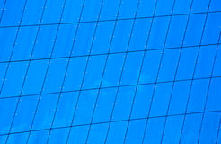 Glass building facade. Building facade made entirely out of blue glass windows forming a grid pattern Royalty Free Stock Photo