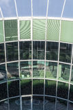 Glass building facade reflecting plants and blue sky Stock Photo