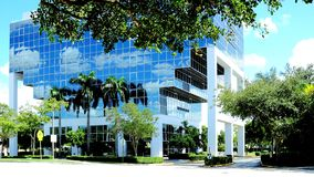 Glass building reflecting sky, clouds and trees Royalty Free Stock Photos