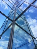 Glass building with reflection of clouds and sky. Modern business center of glass and steel Stock Photo