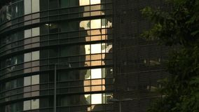 Glass Building With Reflection. Steady, medium close up shot of a glass building with a bright reflection stock video