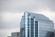 Glass building. Reflective, glass building against a cloudy, gray sky Stock Photography