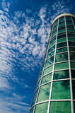 Glass Building Sky. Circular green glass and metal building against blue sky with clouds Stock Photography