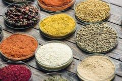 Glass bunkar med olika färgrika kryddor Arkivbild