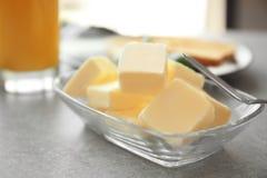 Glass bunke med kuber av smör och kniven Royaltyfri Foto