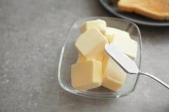 Glass bunke med kuber av smör och kniven Fotografering för Bildbyråer