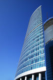 Glass business tower. High and modern office building over deep blue sky Royalty Free Stock Photo