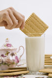 Glass of buttermilk and cookies. A person dunking a cookie in a glass of buttermilk (milk Royalty Free Stock Photo