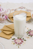 Glass of buttermilk (milk) and cookies. Glass of milk and cookies on a beautiful cloths Royalty Free Stock Images