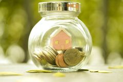 The glass button with the coins and beautiful blur house inside stock photos