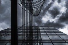 Glass byggnad för hög löneförhöjning under himmel för regnmoln Royaltyfri Bild