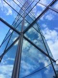 Glass byggnad med reflexion av moln och himmel Arkivfoto