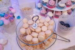 Glass cake stand with tasty pastel French macarons, and bite size profiteroles. Top view of cake stand at a dessert bar for a wedding, party or event, exhibiting Stock Photography