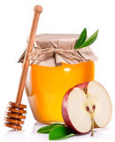 Glass can full of honey, apple and wooden stick. Royalty Free Stock Images