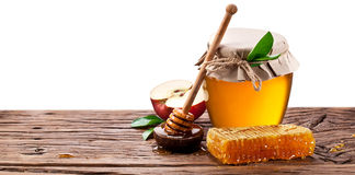 Glass can full of honey, apples  and on old wooden table. Clippi Royalty Free Stock Photography
