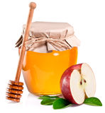 Glass can full of honey, piece of apples and wooden dipper. Stock Image