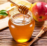Glass can full of honey and wooden dripper. Royalty Free Stock Photography