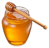 Glass can full of honey and wooden stick on it. Stock Photo