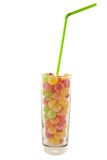 Glass of candies. Glass of multicolor candies as a cocktail with green straw royalty free stock photos