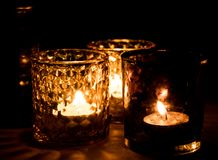 Glass candle holders with tealight candles, warm and cozy atmosphere.  royalty free stock image