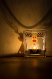 Glass candle with the reindeer on the wooden table.  royalty free stock photos