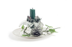 Glass candlestick with green candle. On the silver plate decorated with silver cone and artificial vine stock images