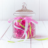 Glass candy jar filled with pink gummy candies. Antique glass candy jar filled with pink gummy candies and tied with three ribbons with the white, green and pink royalty free stock photos