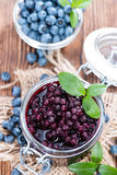 Glass with canned Blueberries. And some fresh fruits royalty free stock photography