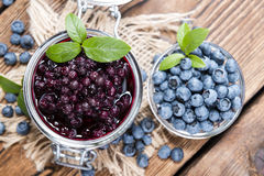 Glass with canned Blueberries. And some fresh fruits stock photography