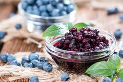 Glass with canned Blueberries. And some fresh fruits Stock Photo