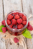 Glass with Canned Raspberries. Glass with a portion of canned raspberries with some fresh fruits on wooden background Stock Photo