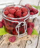Glass with Canned Raspberries. Glass with a portion of canned raspberries with some fresh fruits on wooden background Stock Photography