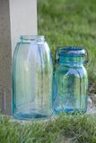 Glass Canning Jars. Blue glass jar with a wire holding the lid and rubber ring onto it, used for canning fruits and vegetables, sitting in the grass royalty free stock photography