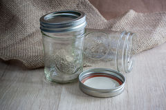 Glass Canning Jars. On a wooden table with burlap behing them Royalty Free Stock Image